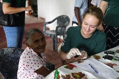 Una volontaria in Sri Lanka fa il test dello zucchero nel sangue e della pressione sanguigna