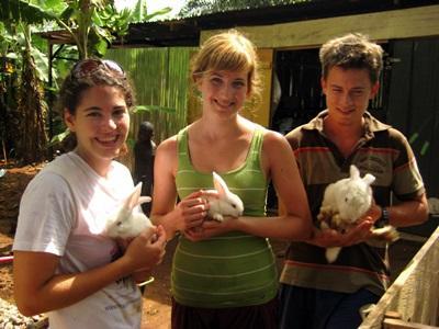 Alcuni volontari posano con i conigli della fattoria sede del progetto di agricoltura biologica in Ghana