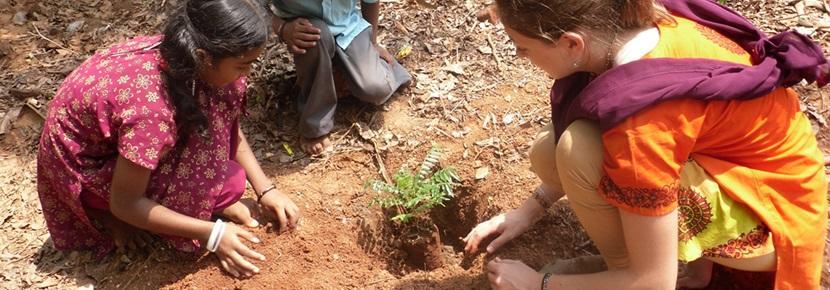 Una volontaria pianta semi con una bambina locale