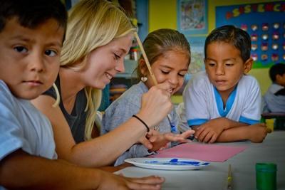 Una volontaria dipinge assieme ai bambini per il progetto di volontariato culturale in Equador