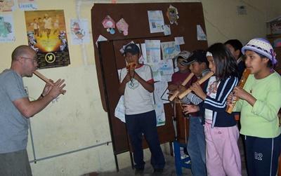 Un volontario insegna agli alunni a suonare il flauto a Cochabamba
