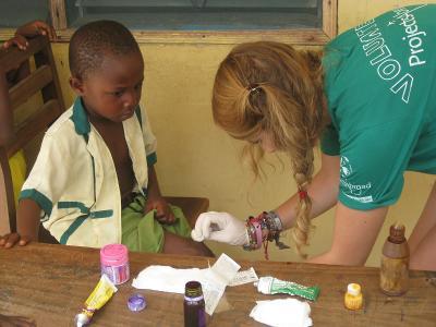 Una volontaria del progetto di Salute Pubblica cura una ferita di un bambino in Ghana