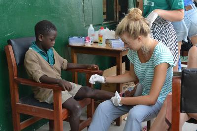 Una volontaria di ProjectsAbroad cura una ferita ad un bambino in Ghana