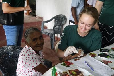 In Sri Lanka, una volontaria controlla i livelli di glicemia a una donna durante le visite alle comunità