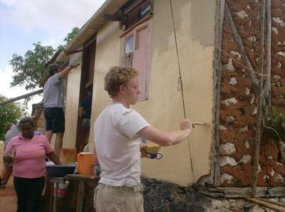Giamaica, un volontario dipinge un edificio durante il campo di costruzioni
