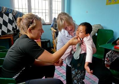 Nepal, due volontarie si prendono cura di un bambino