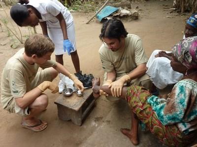 Alcuni volontari medicano una donna durante una visita nei villaggi in Ghana