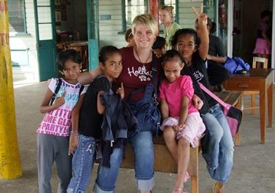 Una volontaria con in braccio i bambini del campo umanitario alle Fiji