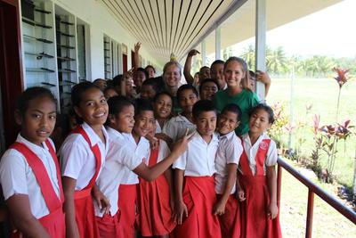 Una volontaria del campo umanitario e lavoro comunitario alle Isole Samoainsieme ai bambini di una scuola locale