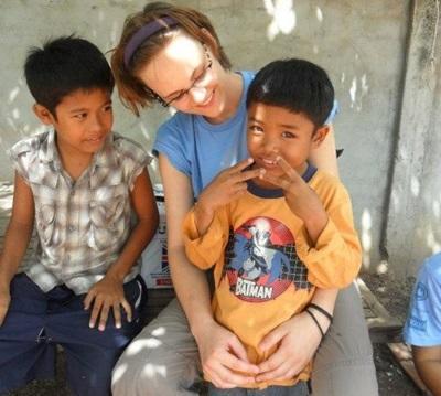 Una volontaria intrattiene alcuni bambini durante un campo umanitario in Cambogia