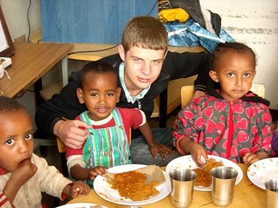 Un volontario assiste alcuni bambini durante i pasti in Etiopia