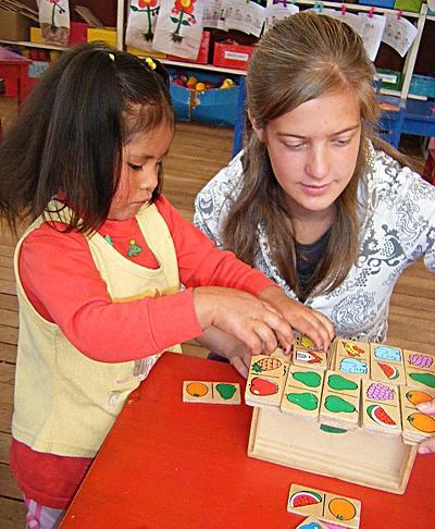 Bambina peruviana impara con l'aiuto di una volontaria