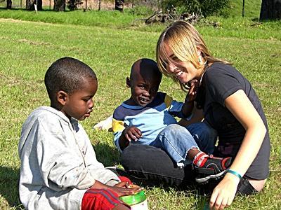 Una volontaria gioca con i bambini in mezzo ad un prato in Sudafrica