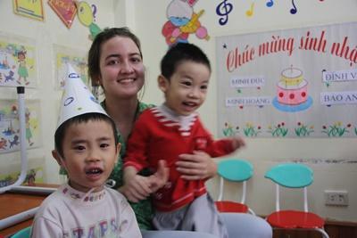 Una volontaria con in braccio i bambini del campo umanitario in Vietnam
