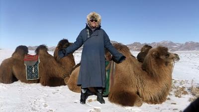 Un volontario posa con dei cammelli in Mongolia