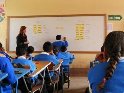 Una volontaria e uno studente durante un esercizio di inglese alla lavagna in una scuola di Cusco