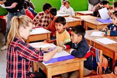 Una volontaria di Projects Abroad aiuta uno studente durante una lezione in Perù