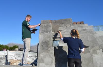Due volontari costruiscono un muro di un centro comunitario alla periferia di Cape Town, Sudafrica