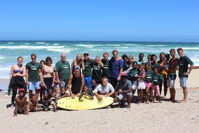 I volontari di Projects Abroad in posa sulla spiaggia di Muizemberg  con i bambini del progetto di surf a Cape Town