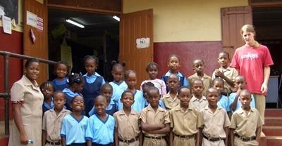 Un volontario del progetti di insegnamento dell'informatica con gli studenti in Giamaica