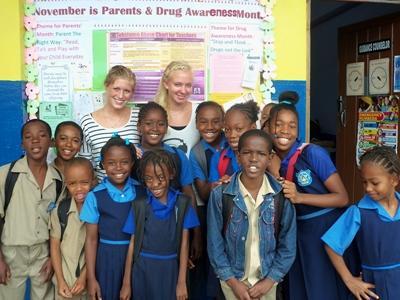 Due volontarie con una classe del progetto di insegnamento dell'informatica in Giamaica
