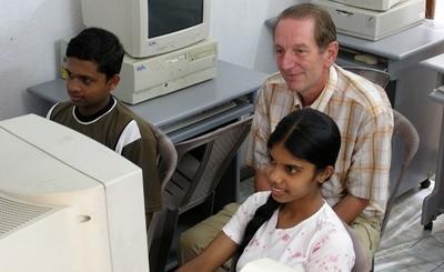 Un volontario del progetto di insegnamento dell'informatico con due studenti srilankesi