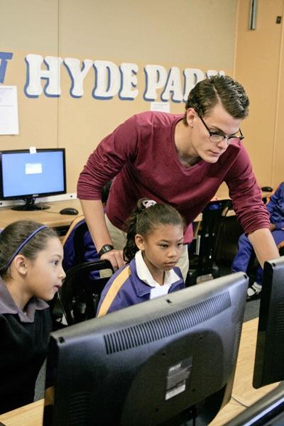 Un volontario impegnato nell'insegnamento dell'informatica in una classe in Sudafrica