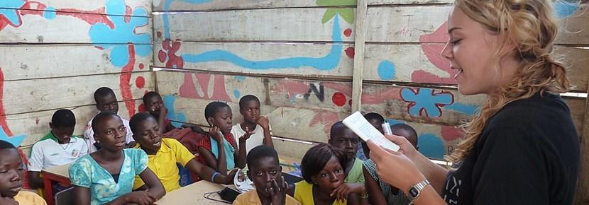 Una volontaria insegna ad alcuni bambini