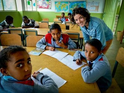 Una volontaria assiste i bambini locali durante una missione di volontariato di insegnamento in Etiopia