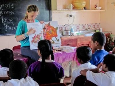 Una volontaria insegna a leggere ai bambini delle Fiji
