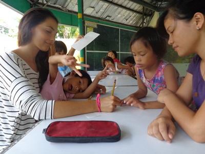 Una volontaria con alcune bambine del progetto di insegnamento alle Filippine