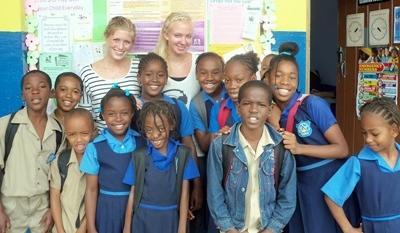 Due volontarie con una classe durante il progetto di insegnamento in Giamaica