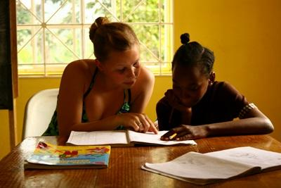 Una volontaria assiste un'alunna a fare i compiti per il progetto di insegnamento in Giamaica