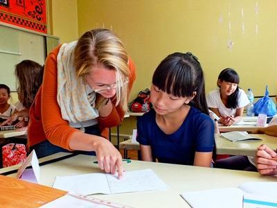 Una volontaria assiste un'alunna a fare i compiti per il progetto di insegnamento ad Ulan Bator