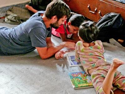 Un volontario assiste gli alunni nelle attività didattiche in Nepal
