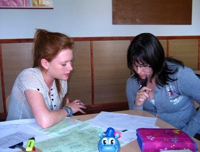 Una volontaria assiste un'alunna a fare i compiti per il progetto di insegnamento a Brasov