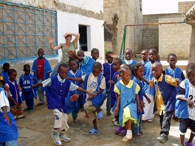 Una volontaria aiuta gli alunni nelle attività didattiche in Senegal