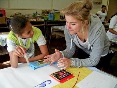 Una volontaria assiste un'alunna a fare i compiti per il progetto di insegnamento a Cape Town