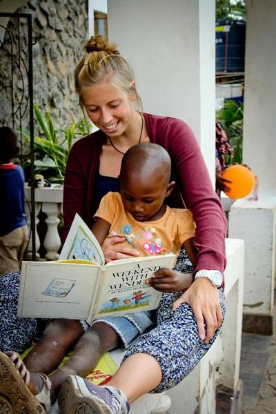 Una volontaria in missione per il progetto di insegnamento assieme ad una giovane studentessa in Tanzania