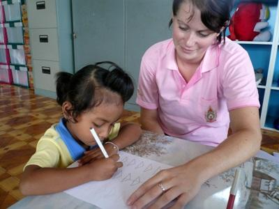 Una volontaria assiste un'alunna a fare i compiti per il progetto di insegnamento in Thailandia