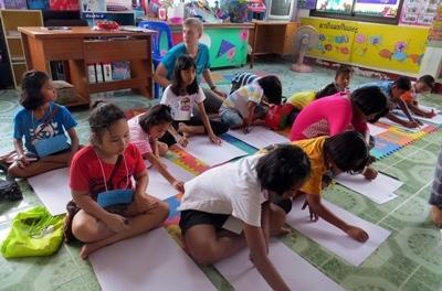 Un volontario del progetto di insegnamento con una classe di alunni in Thailandia
