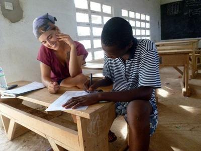 Una volontaria aiuta un giovane studente di una scuola del Togo