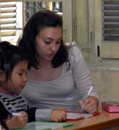 Una volontaria assiste un'alunna a fare i compiti per il progetto di insegnamento in Vietnam