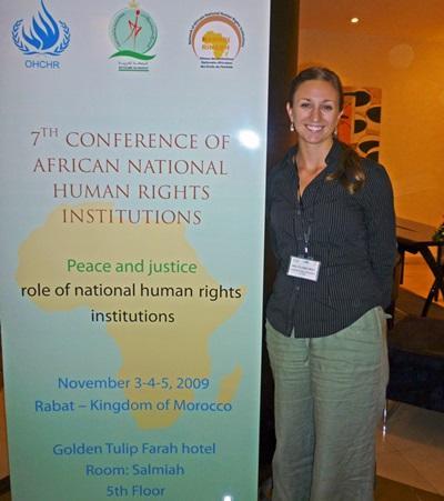 Una volontaria posa con un cartellone di una campagna sui diritti umani in Marocco