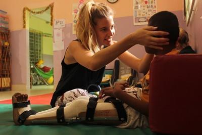 Cambogia, una volontaria fisioterapista aiuta un bambino durante la riabilitazione