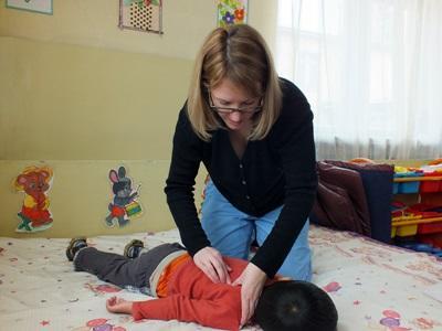Una volontaria del progetto di fisioterapia  pratica la riabilitazione di un bambino locale