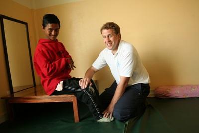 Un volontario del progetto di fisioterapia con un piccolo paziente in Nepal
