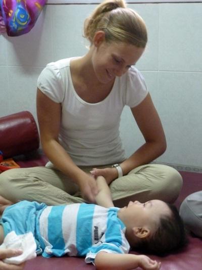Una volontaria del progetto di fisioterapia si prende cura di un paziente in Vietnam