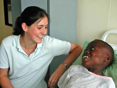 Ghana, una volontaria del progetto di infermieristica con un giovane paziente