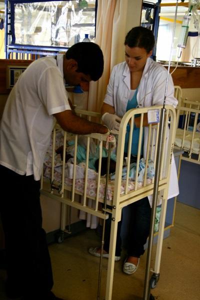 Una volontaria del progetto di infermieristica assiste un neonato con l'aiuto dello staff locale